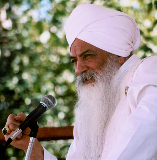 Yogi Bhajan at a microphone, with trees in the background